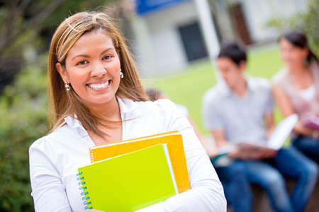 adult learning: Female student holding notebooks and looking very happy