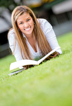 Woman studying outdoors reading a book and looking very happy  Stock Photo - 16587240