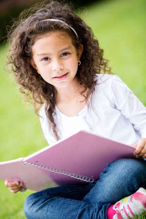 niños estudiando: Colegiala linda en el parque de la celebración de una computadora portátil