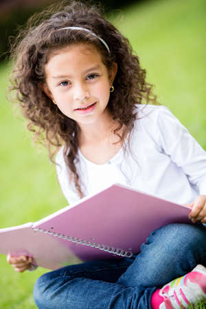 Cute schoolgirl at the park holding a notebook  Stock Photo - 16586966