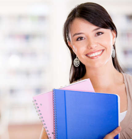 Happy female student at the university holding a notebook  Stock Photo - 16586878