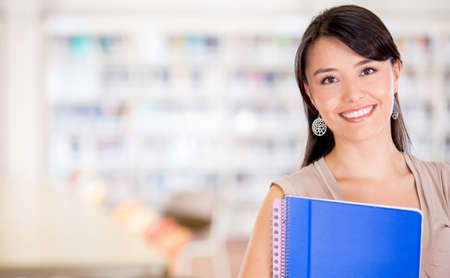 Female student at the library looking very happy  Stock Photo - 16586953