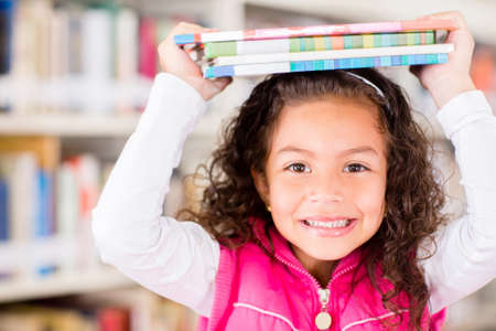 Happy girl at the library holding books  Stock Photo - 16586886