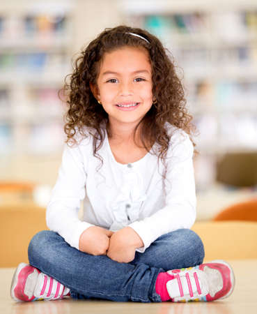 Happy schoolgirl at the library sitting on top of a table Stock Photo - 16586837