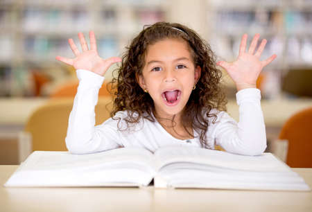 Excited girl reading a book at the school library photo