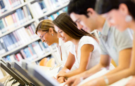 Group of students researching at the library on computers  photo