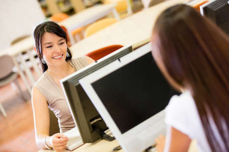 Female students researching on a computer at the library  Stock Photo - 16586885