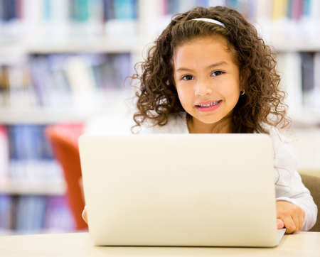 hispanic children: Little girl using a computer at the school
