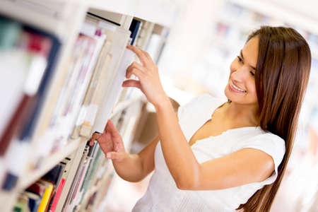 Female student looking for a book at the library photo
