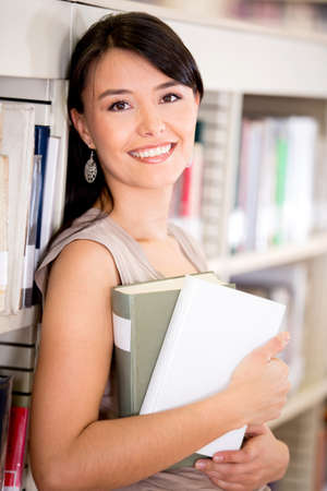 University student carrying books at the library Stock Photo - 16587239