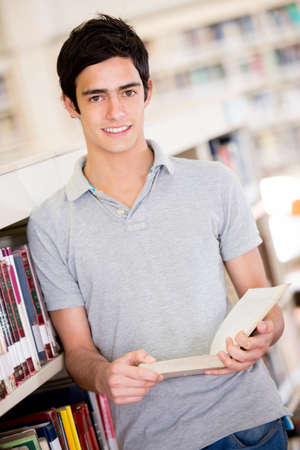 Male student at the library holding a book and smiling Stock Photo - 16586956
