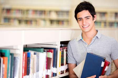 hispanic student: Feliz estudiante masculino que sostiene los libros en la biblioteca