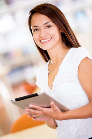 Woman with an e-book reader at the library Stock Photo - 16586962
