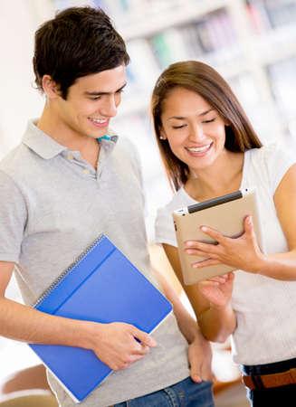 hispanic student: Los estudiantes universitarios con un tablet PC con una aplicaci�n