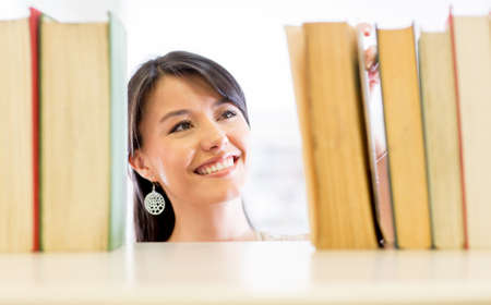 Woman looking for a book at the library Stock Photo - 16587229