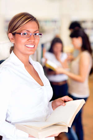 Female student at the library holding a book Stock Photo - 16586836