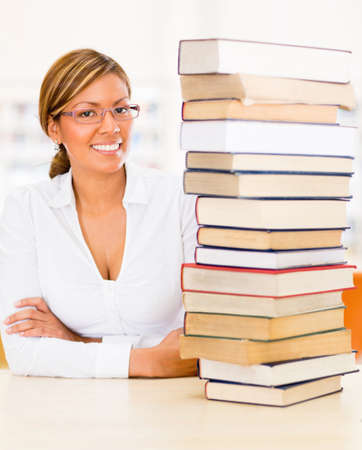 geeky: Geeky student at the library with a pile of books to read Stock Photo