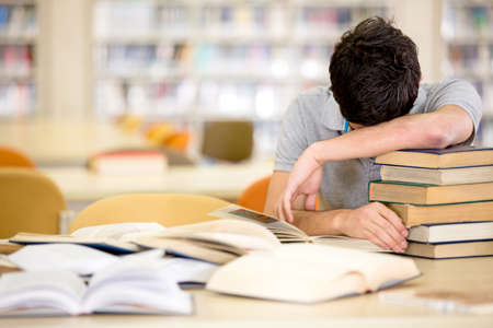 Exhausted male student with a pile of books photo