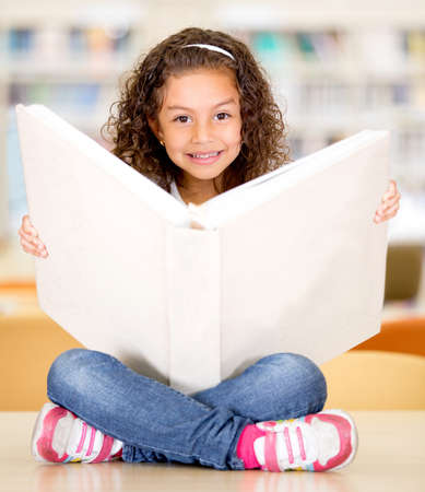Happy little girl at the library reading a book Stock Photo - 16586961