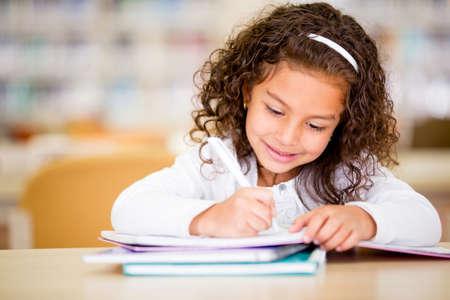 nios hispanos: Chica estudiando en la escuela parece muy feliz