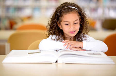 children reading: Young school girl reading a book at the library Stock Photo