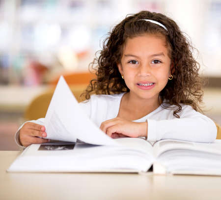 Happy girl reading a book at the school library Stock Photo - 16586887