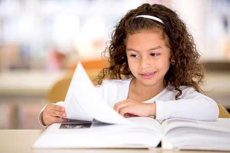 bambini che leggono: Studentessa presso la biblioteca a leggere un libro Archivio Fotografico