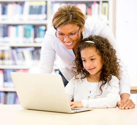 teacher: TIC profesor con un estudiante joven que usa el ordenador Foto de archivo