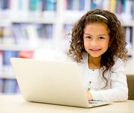 Girl using a laptop computer at school photo