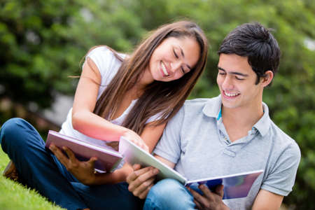 latin students: Young couple studying at the park and smiling