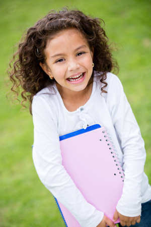 Young female student holding notebooks and looking happy Stock Photo - 16586889