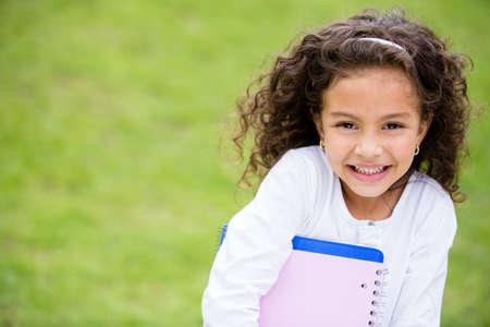 happy young: Al aire libre Feliz colegiala llevan cuadernos y sonriente
