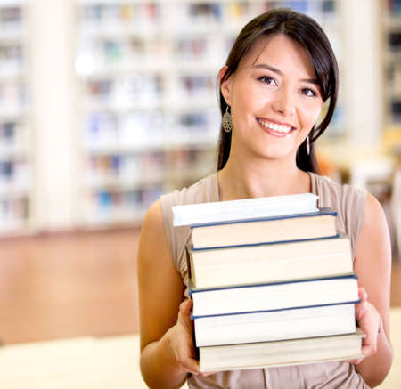 Female student carrying a pile of books at the library Stock Photo - 16586890