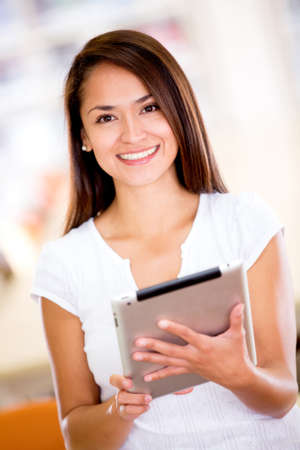 Happy female student using a tablet computer photo