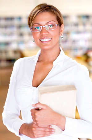 Beautiful librarian holding a book at the library Stock Photo - 16586946