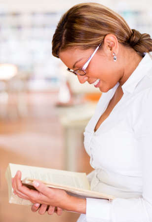 Happy woman at the library reading a book Stock Photo - 16586875