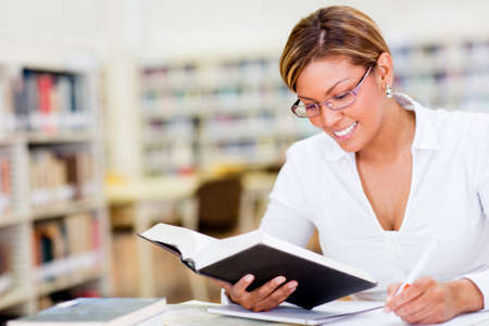 Beautiful happy woman studying at the library photo
