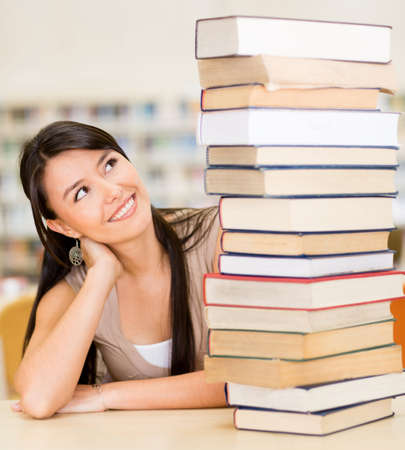 Female student with a pile of books at the library Stock Photo - 16586884
