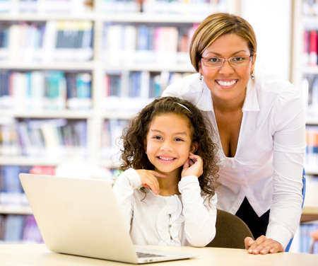 Girl with a computers teacher looking very happy Stock Photo - 16586881