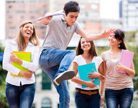 estudiantes universitarios: Grupo de estudiantes que se divierten mirando a un hombre que salta Foto de archivo