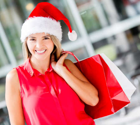 Beautiful female Santa shopping and looking very happy photo