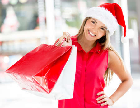 Happy woman with her Christmas purchases wearing a Santa hat photo