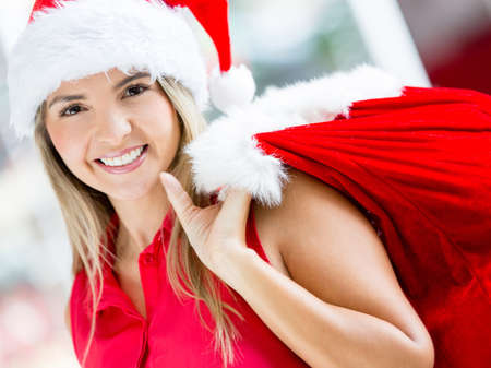 Happy female Santa carrying a gift sack and smiling Stock Photo - 16691543