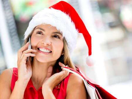 Female Santa talking on the phone looking happy photo