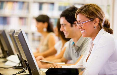 biblioteca: Los estudiantes investigan en l�nea en la biblioteca en los equipos Foto de archivo