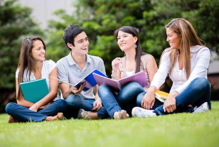 estudiantes universitarios: Feliz grupo de estudiantes sentados en el parque hablando Foto de archivo