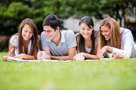 hispanic student: Group of students outdoors studying and looking happy