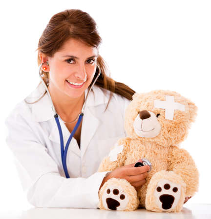 Doctor fixing a sick teddy bear - isolated over a white background photo