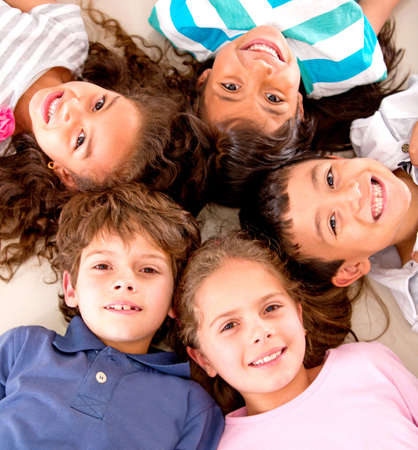 latin kids: Happy group of kids lying on the floor with heads together