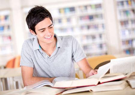 hispanic student: Hombre estudiar en la biblioteca con un mont�n de libros Foto de archivo